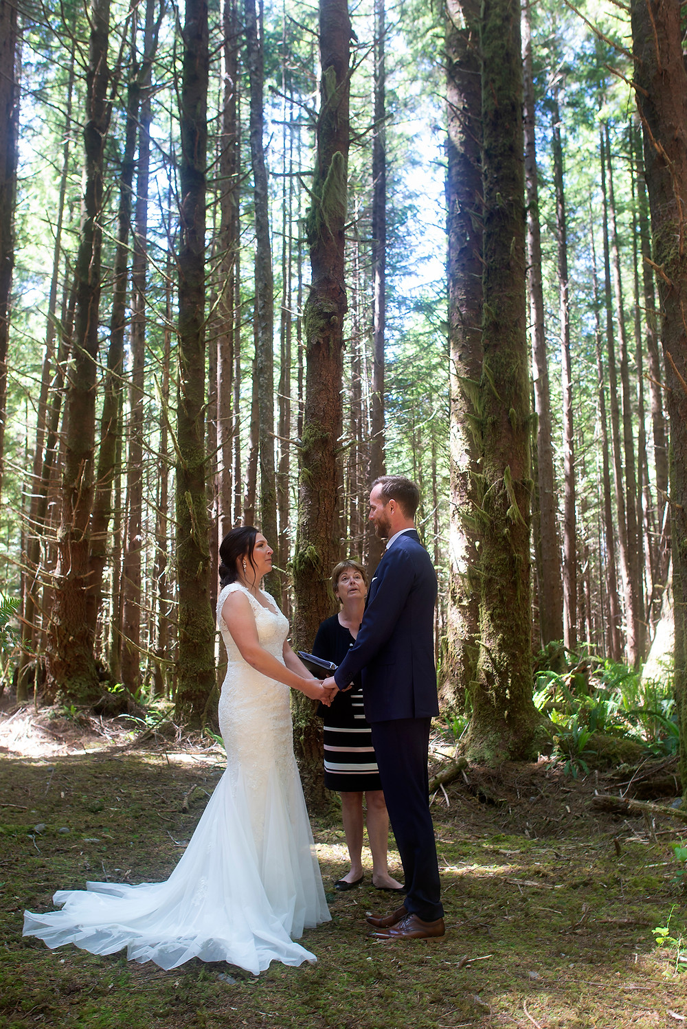 Bride and groom hold hands amongst the trees at a forest wedding in Tofino. Photographed by Kaitlyn Shea.