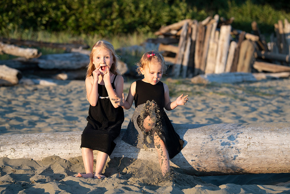 Sisters sit on a log during their family photos in tofino. photographed by Tofino photographer Kaitlyn Shea.