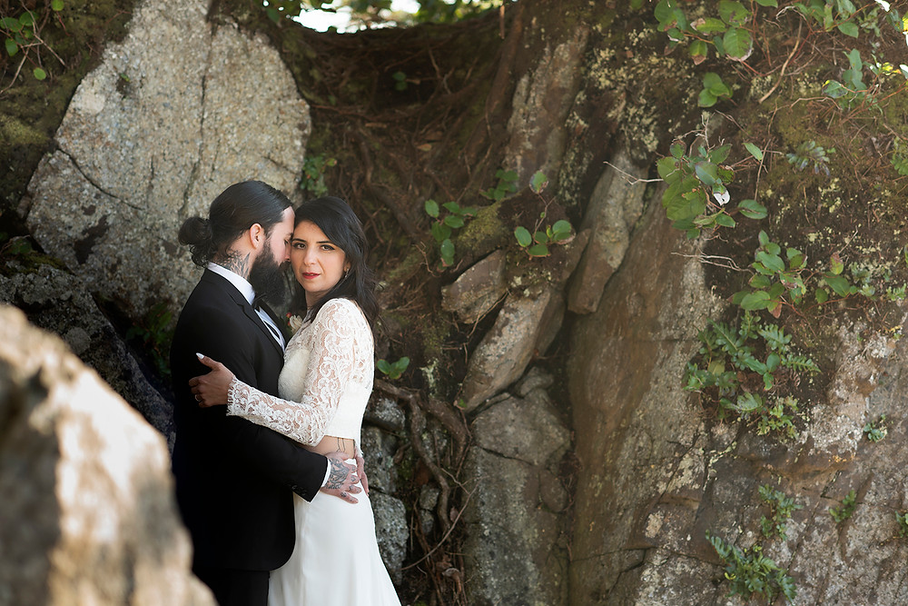 Bride and groom hug amongst the rock after eloping to Ucluelet. Photographed by Kaitlyn Shea.