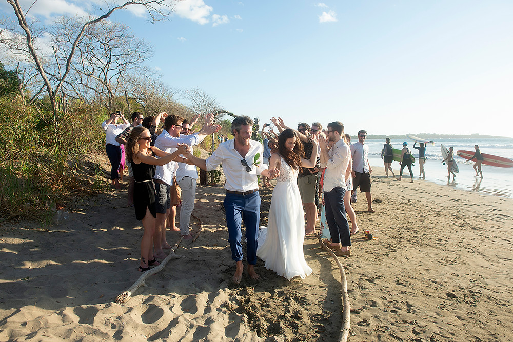 Couple runs down aisle while friends holler at their destination wedding in Playa Grande, Costa Rica. Photographed by Kaitlyn Shea.