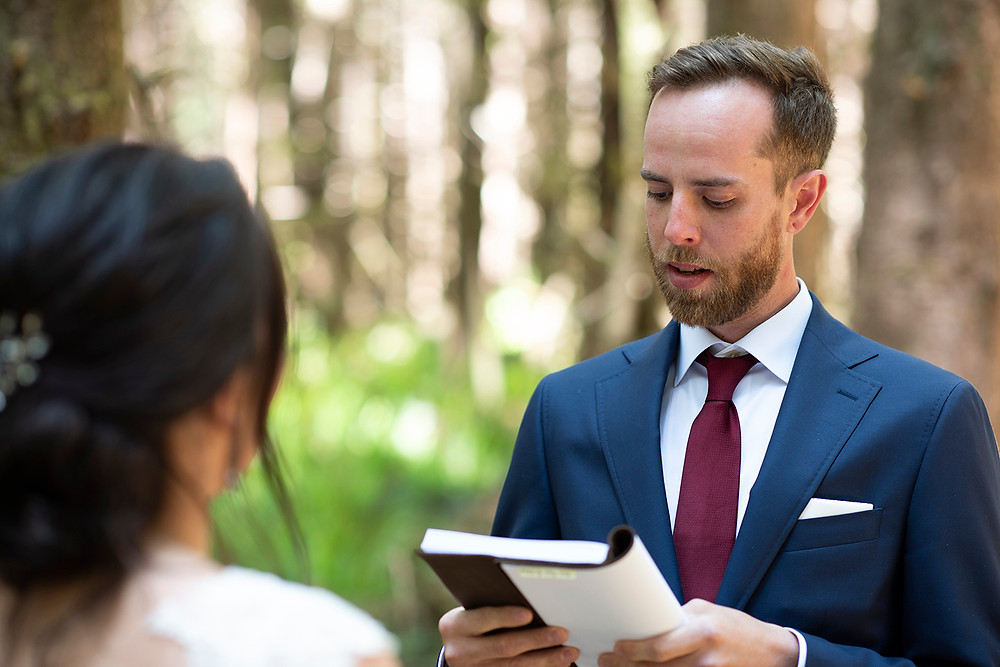 Groom reads his vows at a forest wedding in Tofino. Photographed by Kaitlyn Shea.