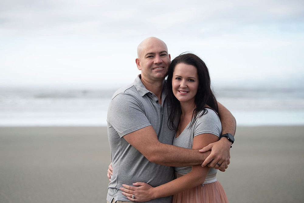 Couple hugs during their family photography session in Tofino. Photographed by Kaitlyn Shea.