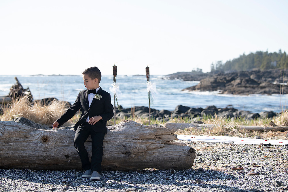 Little boy sits by the sea at an Ucluelet Elopement. Photographed by Kaitlyn Shea.