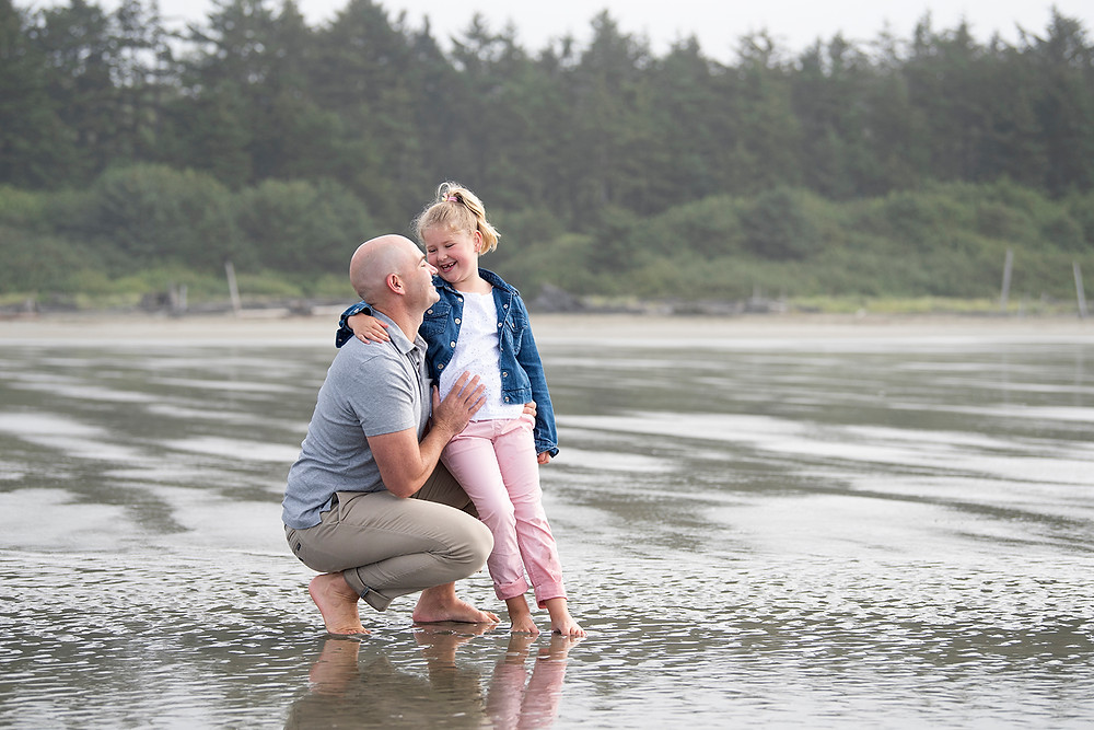 Father and daughter laugh during a family photography session. Photographed by Kaitlyn Shea.