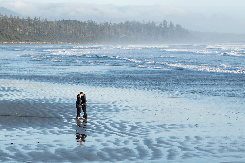Couple kisses on Long Beach during their Tofino engagement photos. Photographed by Tofino photographer Kaitlyn Shea.