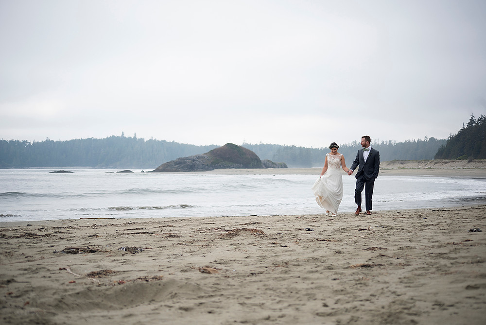 bride and groom stroll down the beach at Schooner Cove wedding in Tofino. Photographed by Kaitlyn Shea