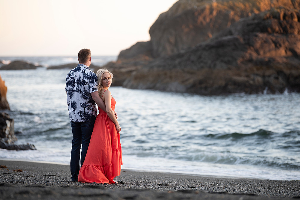 engaged couple embrace on the beach in Tofino. Photographed by Kaitlyn Shea.