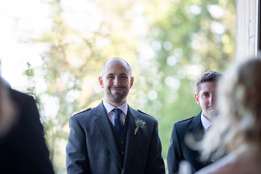 Grooms smiles as bride enters wedding ceremony at Sea Cider Victoria. Photographed by Kaitlyn Shea.