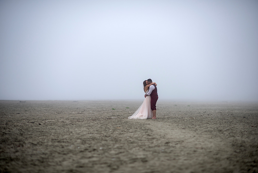 bride and groom hug in the fog at tofino beach wedding at Long Beach Lodge. Photographed by Kaitlyn Shea
