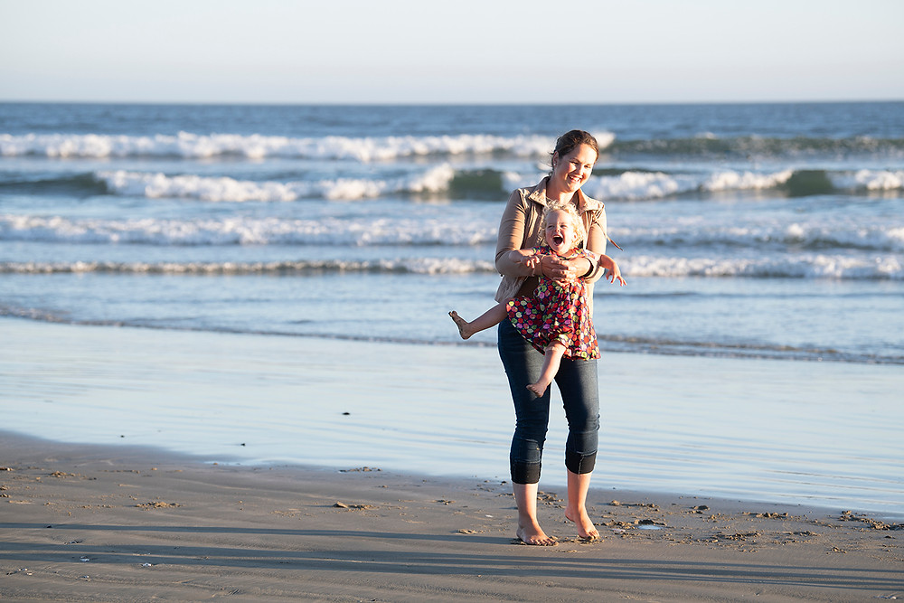 Mom and daughter laugh on the beach during their family photos in Tofino. Photographed by Kaitlyn Shea.