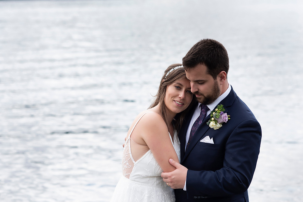 Bride smiles as her husband holds her close at their wedding in August on Vancouver Island. Photographed by Kaitlyn Shea.