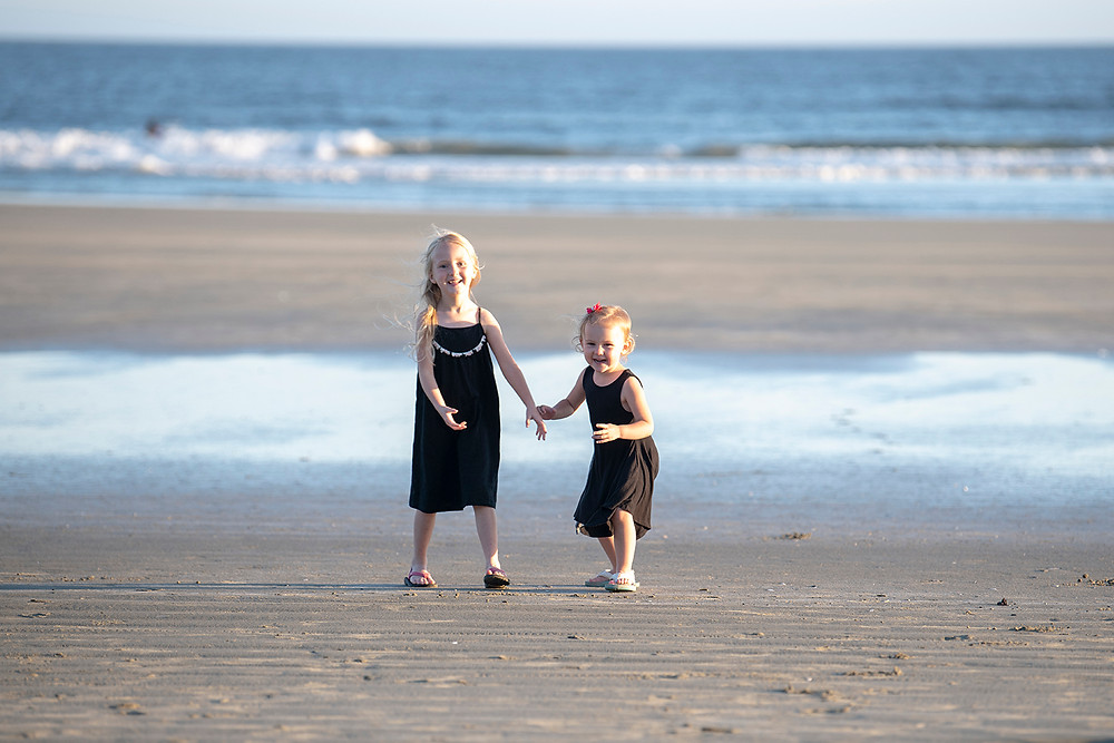 Sisters smile on the beach during their family photos in tofino. photographed by Tofino photographer Kaitlyn Shea.