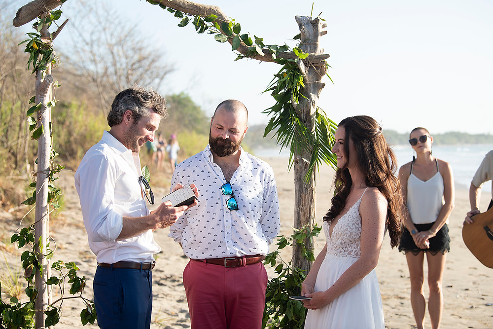 Groom reads his vows to the bride at their destination wedding in Playa Grande, Costa Rica. Photographed by Kaitlyn Shea.