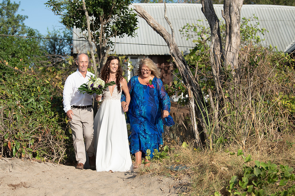 Bride walks down aisle with her parents at a destination wedding in Playa Grande, Costa Rica. Photographed by Kaitlyn Shea.
