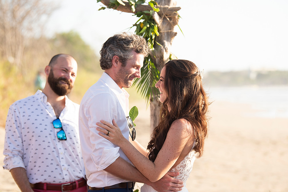 Bride and groom hold each other at their destination wedding in Playa Grande, Costa Rica. Photographed by Kaitlyn Shea.