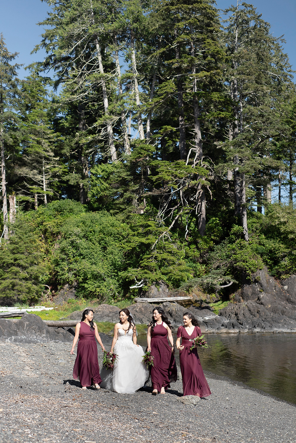 Bride and bridesmaids walk down the beach together at a Ucluelet wedding at Black Rock Resort. Photographed by Ucluelet Photographer Kaitlyn Shea.