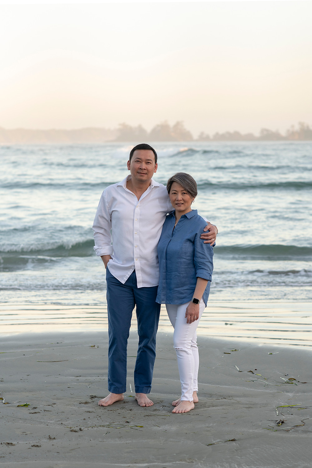 parents stand togther and smile for the camera during family pictures in Tofino | Photographed by Kaitlyn Shea
