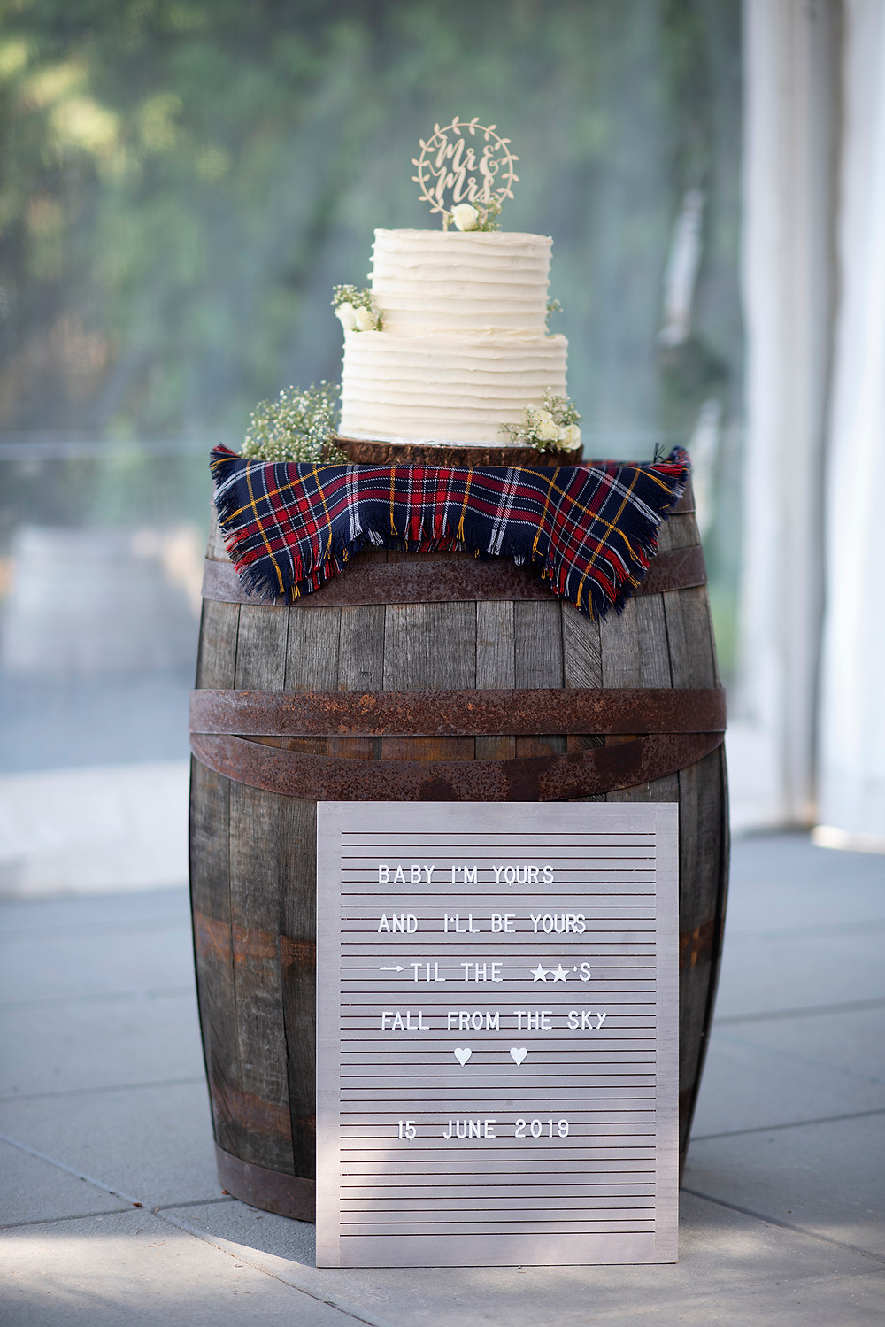 Wedding cake sits on top of cider barrel at Sea Cider Victoria. Photographed by Vancouver Island Photographer Kaitlyn Shea.