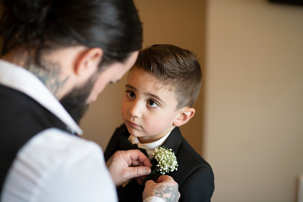 Little boy gets his boutonniere pinned on before an elopement in Ucluelet. Photographed by Kaitlyn Shea.