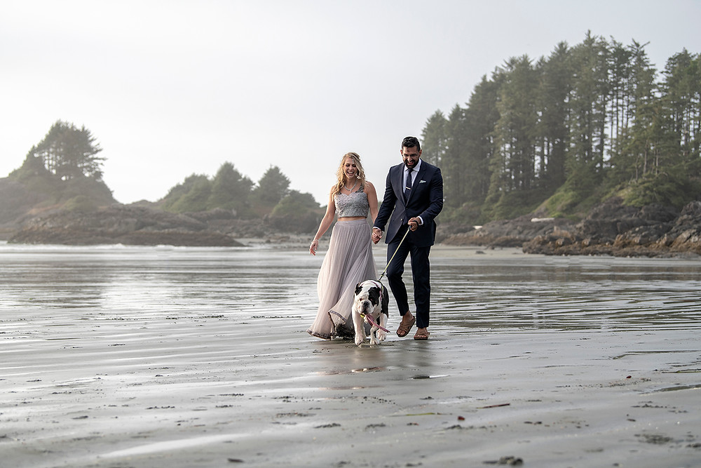 Bride and groom walking with their dog at their small wedding in Tofino. Photographed by Tofino wedding photographer Kaitlyn Shea.