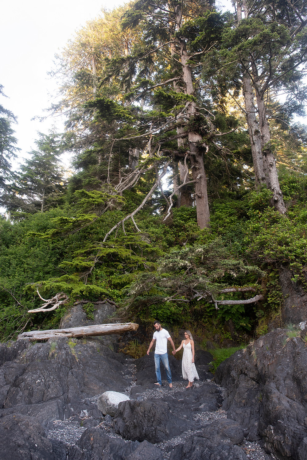 Couple walks on rock during their engagement photos in Ucluelet. photographed by Tofino photographer Kaitlyn Shea.