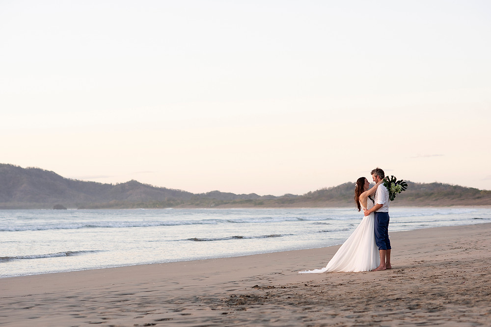 Bride and groom embrace during their destination wedding on Playa Grande in Costa Rica. Photographed by Kaitlyn Shea.