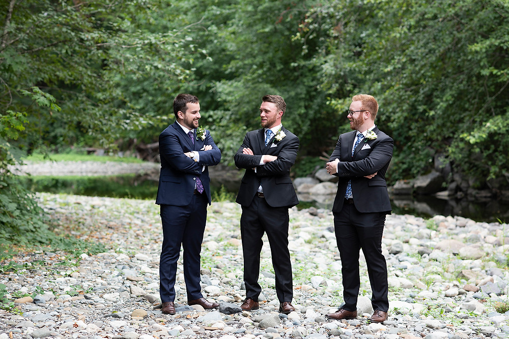 Groomsmen stand at the river at August Wedding on Vancouver Island. Photographed by Kaitlyn Shea.