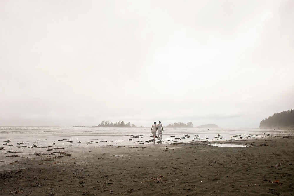 couple walking on beach at destination wedding in Tofino. Photographed by Kaitlyn Shea.