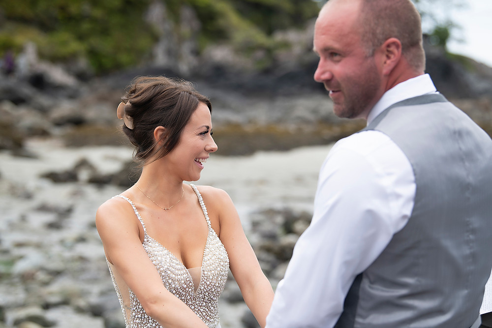 Bride and groom hold hands during an Bride and groom hold rings during an elopement in Tofino. Photographed by Kaitlyn Shea.