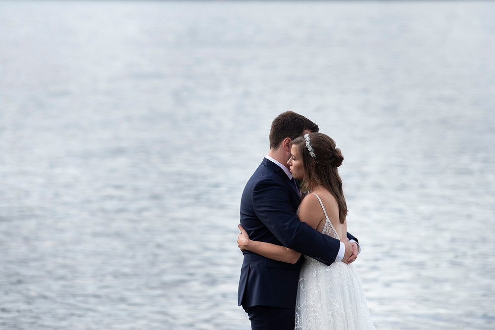 Newly married couple have a long hug at the beach on Port Alberni at their August wedding on Vancouver Island. Photographed by Kaitlyn Shea.
