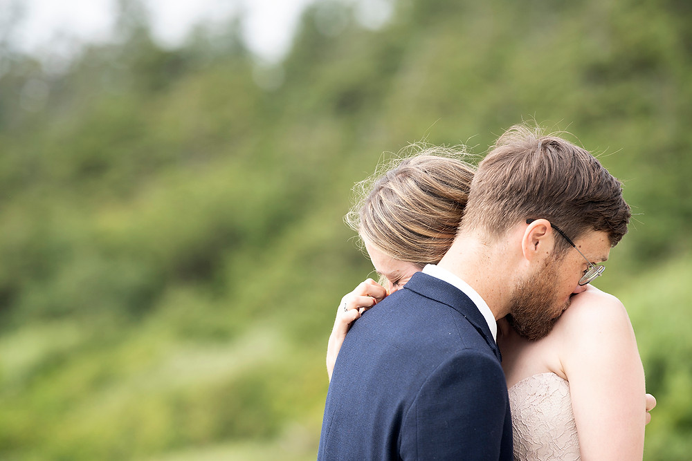 Couple embraces at their beach elopement in Tofino. Photographed by Kaitlyn Shea.