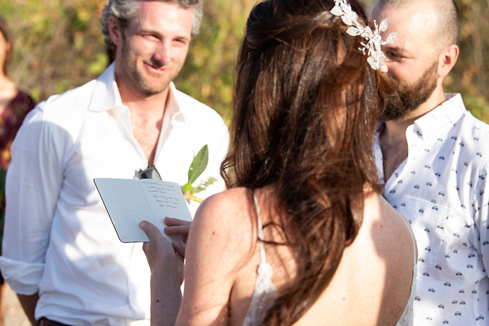 Happy bride reads her vows at a destination wedding in Playa Grande, Costa Rica. Photographed by Kaitlyn Shea.