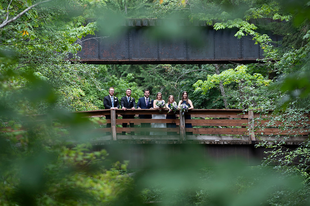 Bridal party stand on bridge at August wedding on Vancouver Island. Photographed by Kaitlyn Shea.