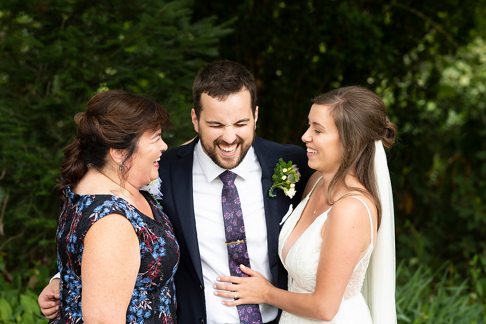 Mother of the groom and bride laugh with the groom at August wedding on Vancouver Island. Photographed by Kaitlyn Shea.