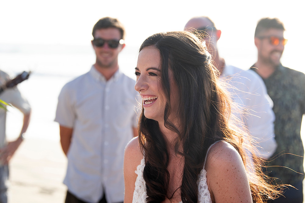 Bride laughs during their ceremony at a destination wedding in Playa Grande. Photographed by Kaitlyn Shea.