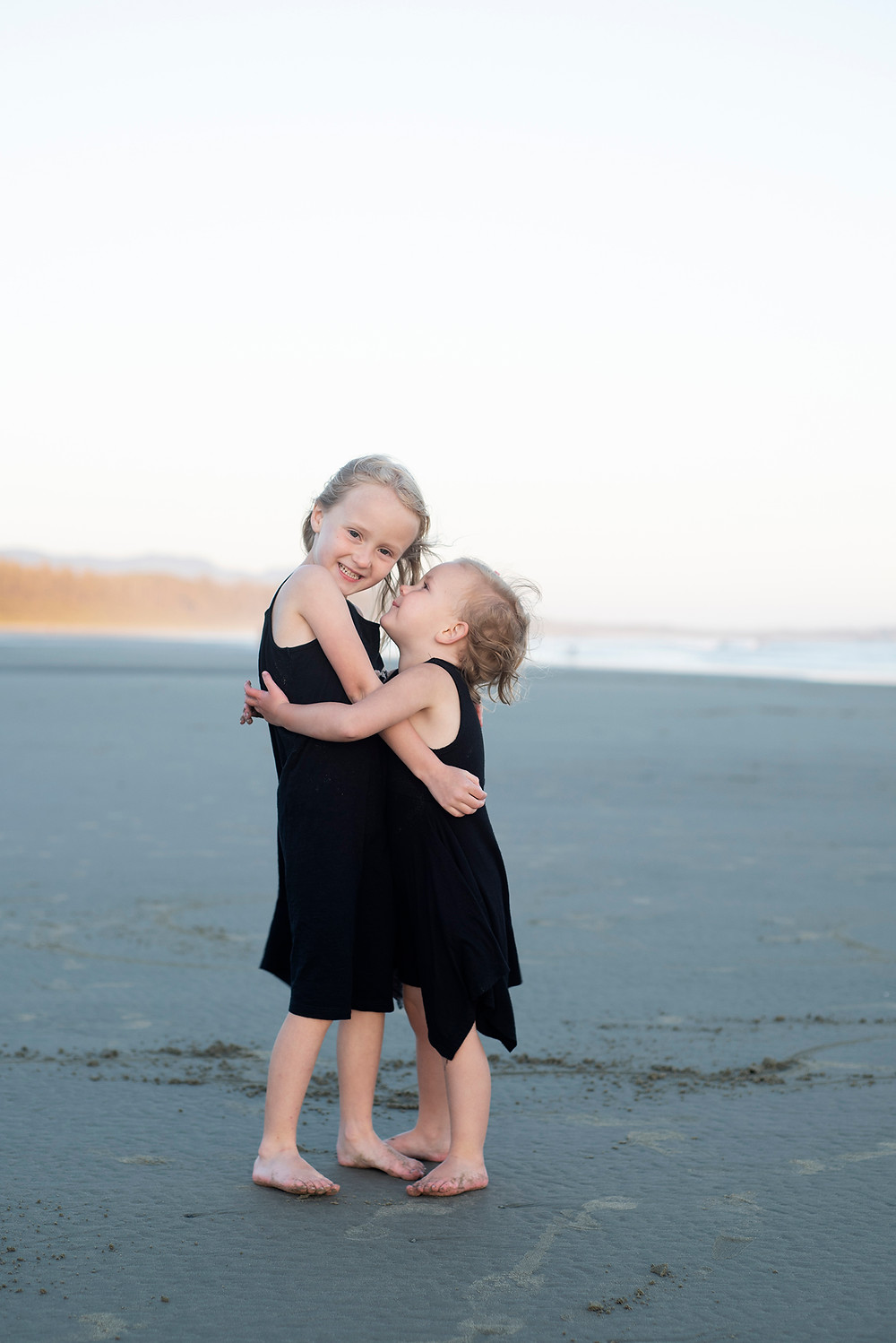 Sisters hug on Long Beach during family photos in Tofino. Photographed by Kaitlyn Shea.