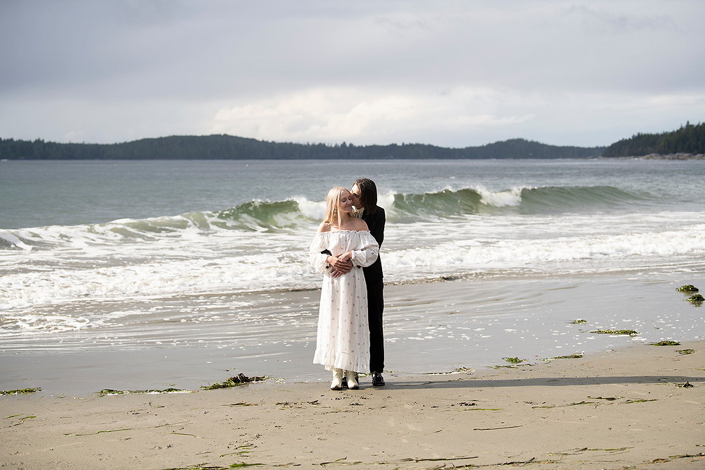 Groom kisses his wife at their Tofino wedding at Tonquin Beach. Photographed by Tofino wedding photographer Kaitlyn Shea.