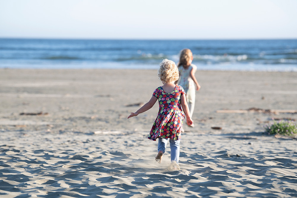 Sisters run toward the ocean during family photos in Tofino. Photographed by Kaitlyn Shea.