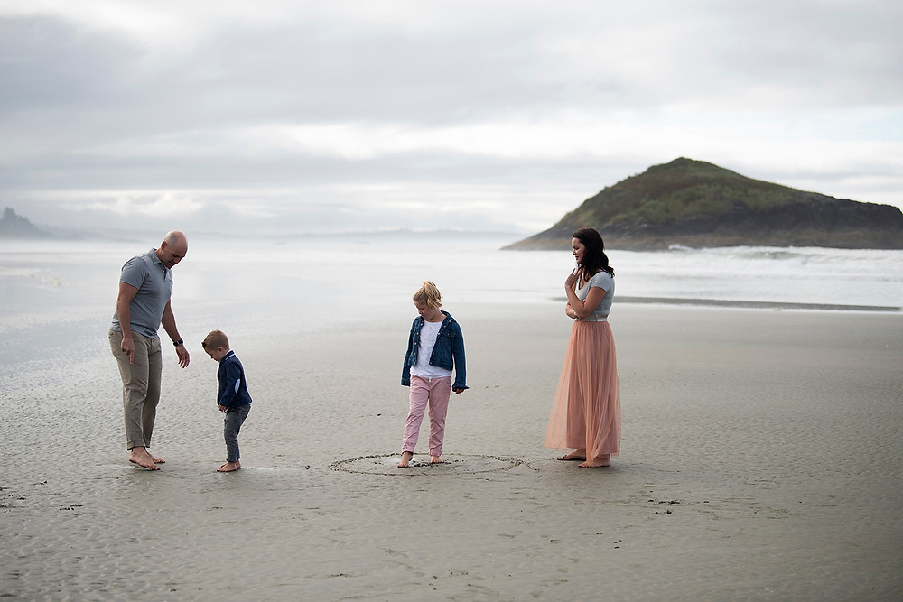 Family hangs out together on Long Beach during their family photography session in Tofino. Photographed by Kaitlyn Shea.