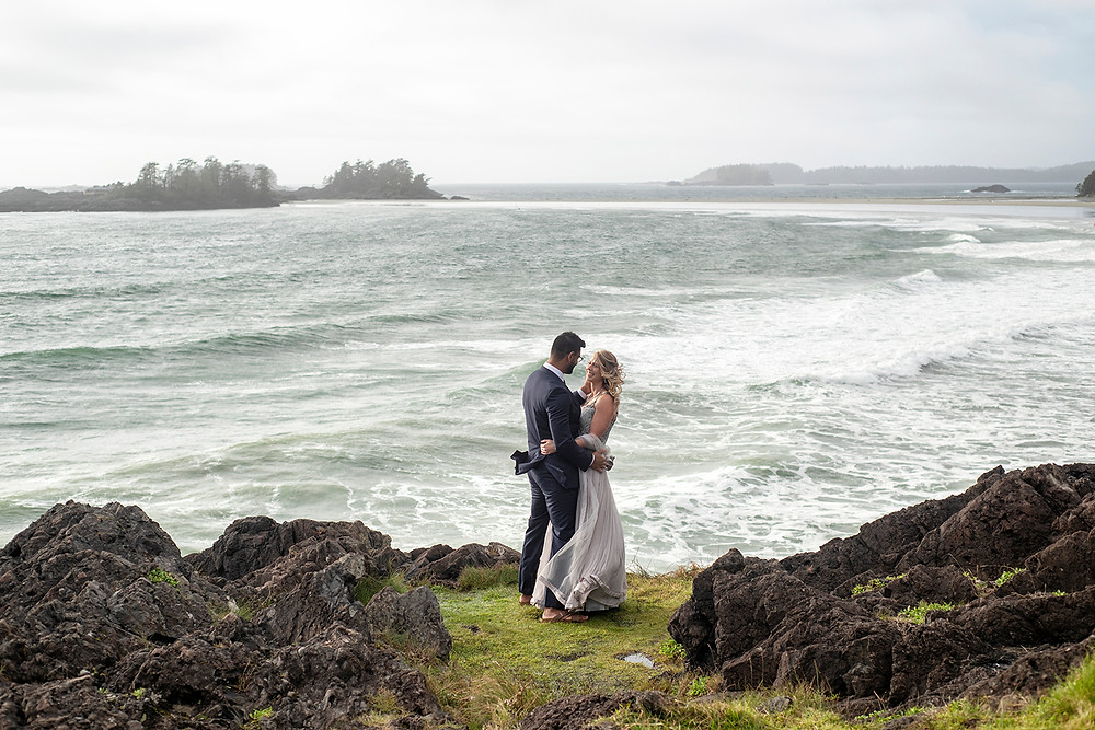 Man and woman hold each other on Pettinger Point at their small wedding in Tofino. Photographed by Tofino wedding photographer Kaitlyn Shea.
