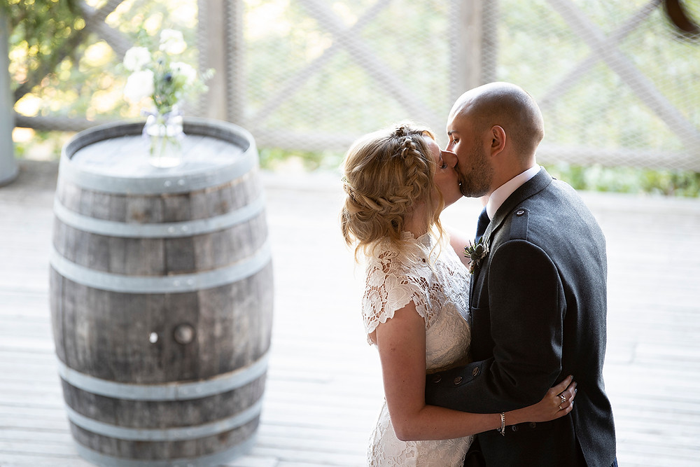 Bride and groom kiss during their wedding ceremony at Sea Cider in Victoria. Photographed by Kaitlyn Shea.