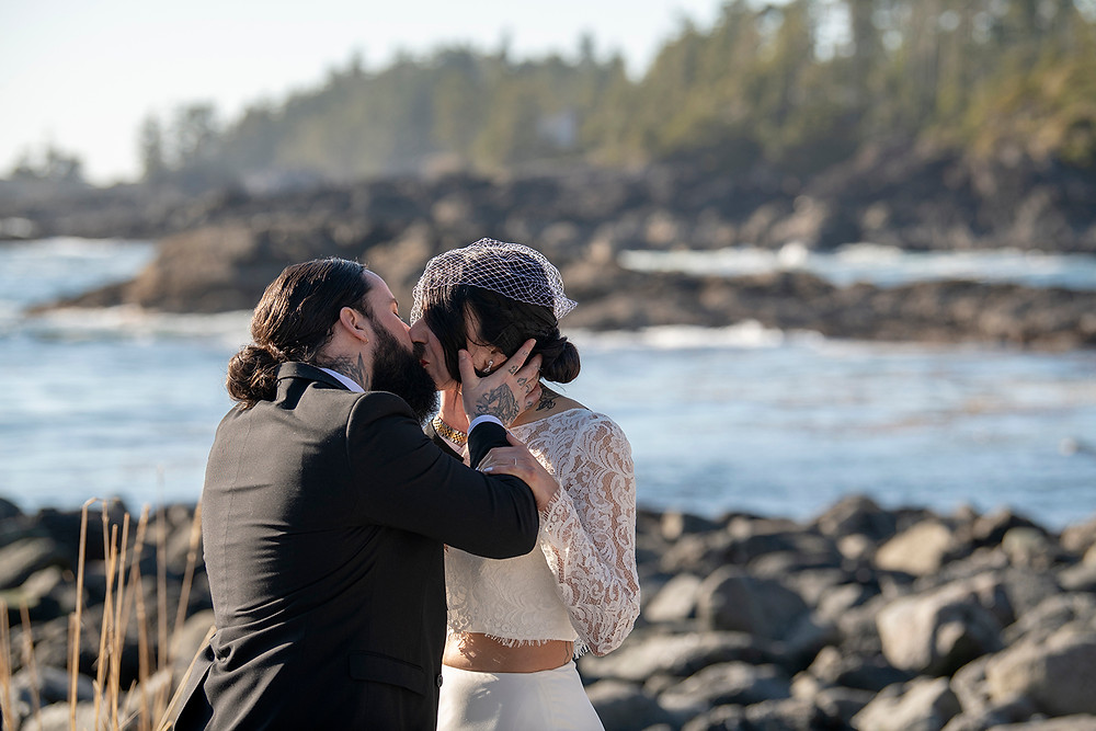 Bride and groom share their first kiss as a married couple while eloping in Ucluelet. Photographed by Kaitlyn Shea.