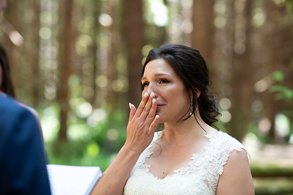 Bride holds back tears during wedding ceremony in the forest in Tofino. Photographed by Kaitlyn Shea.