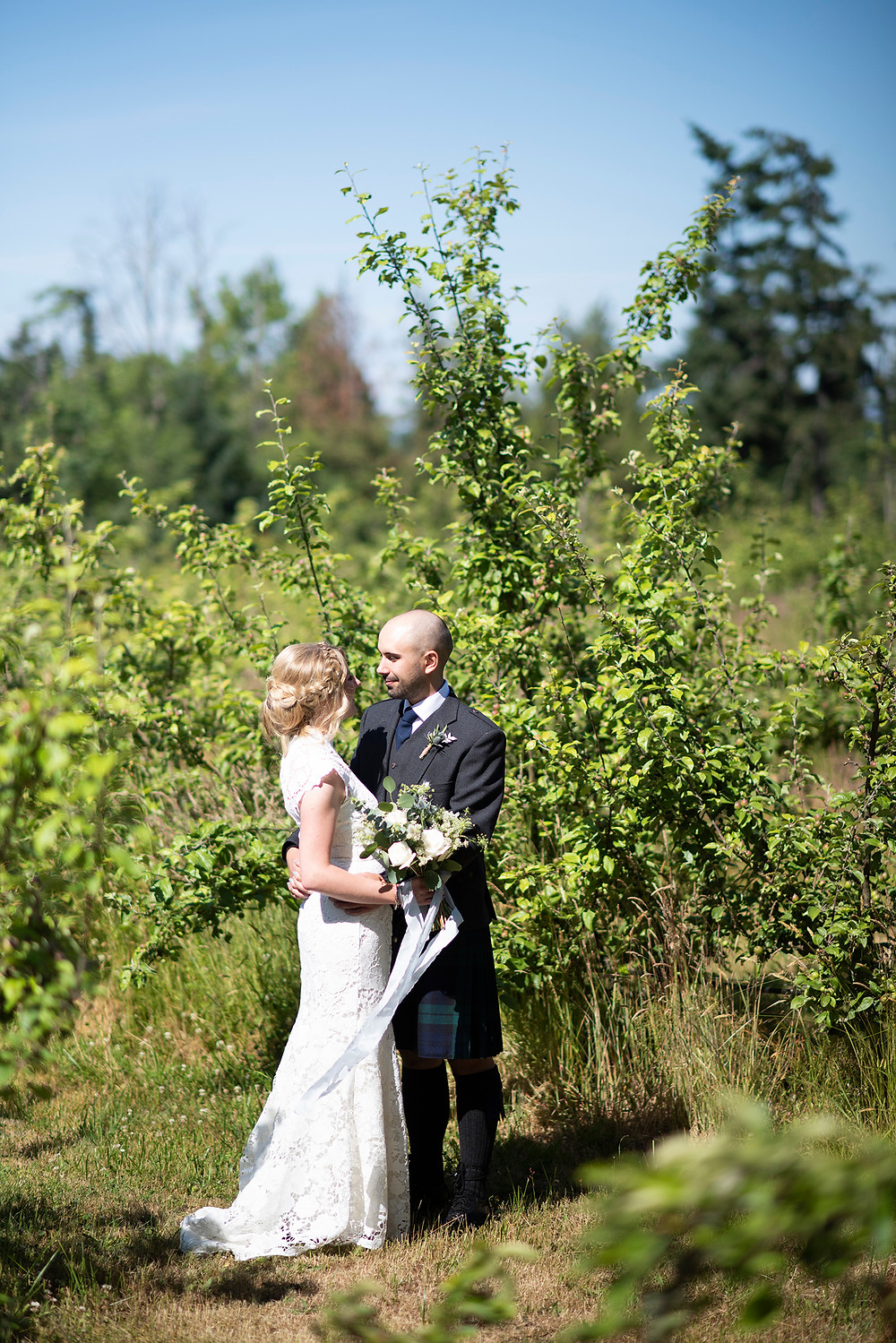 Bride and groom hold each other tightly in the orchard at Sea Cider on Vancouver Island. Photographed by Tofino photographer Kaitlyn Shea.