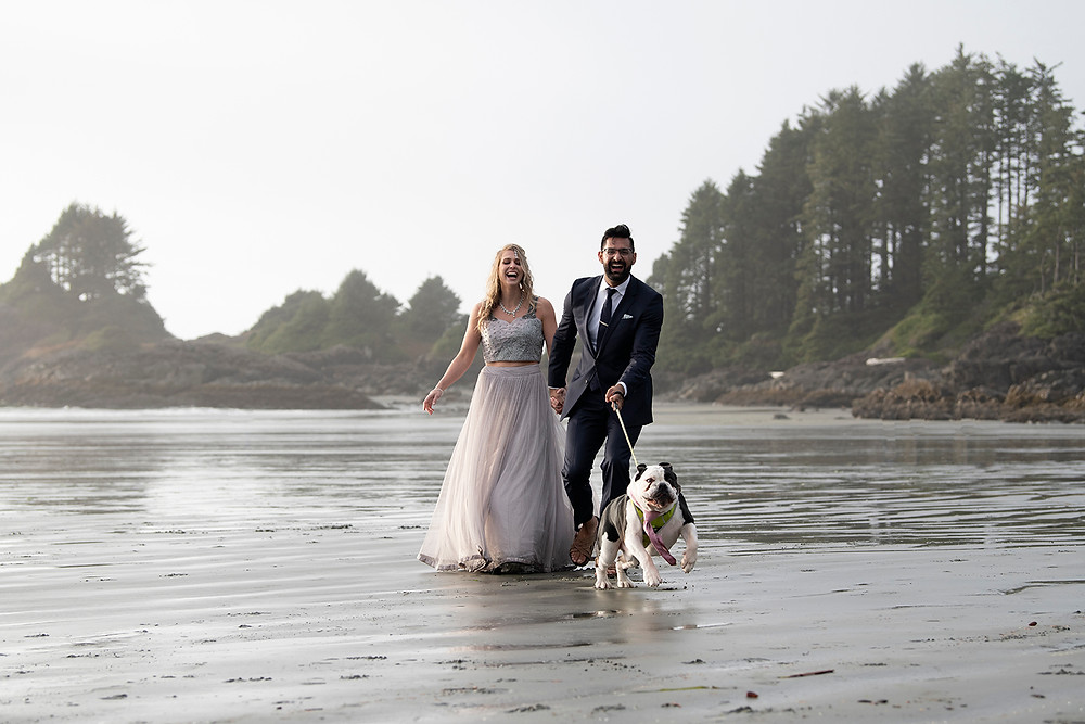 Couple getting pulled by their dog at their small wedding in Tofino. Photographed by Tofino wedding photographer Kaitlyn Shea.
