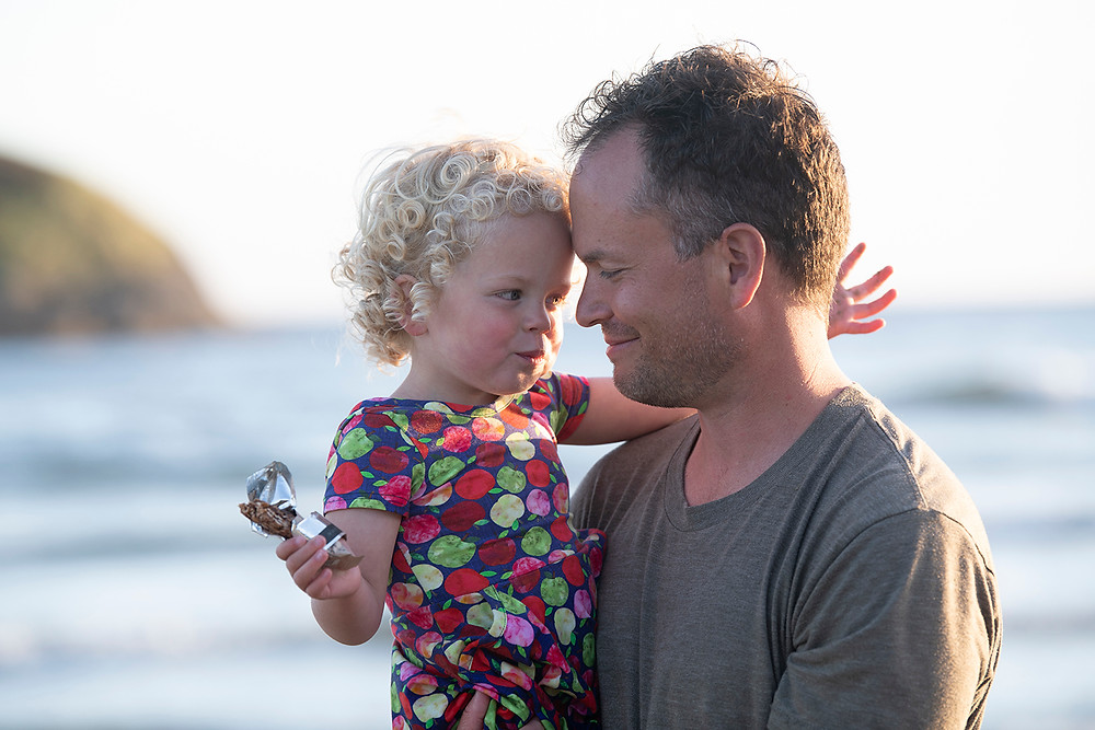Dad and daughter smile at one another during a family photography session in Tofino. Photographed by Kaitlyn Shea.