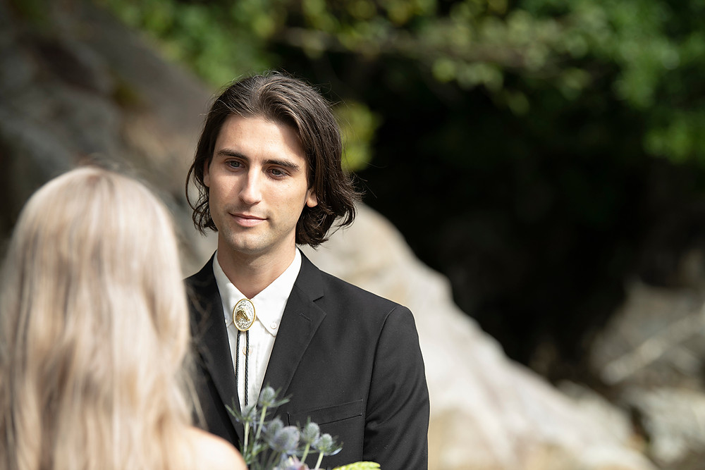 groom looks at his wife lovingly at their Tofino wedding at Tonquin Beach. Photographed by Tofino wedding photographer Kaitlyn Shea.