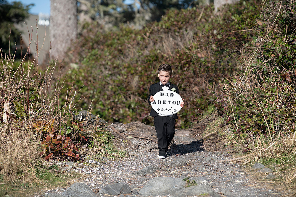 Bride and Grooms youngest son walks down aisle at their elopement in Ucluelet. Photographed by Kaitlyn Shea.