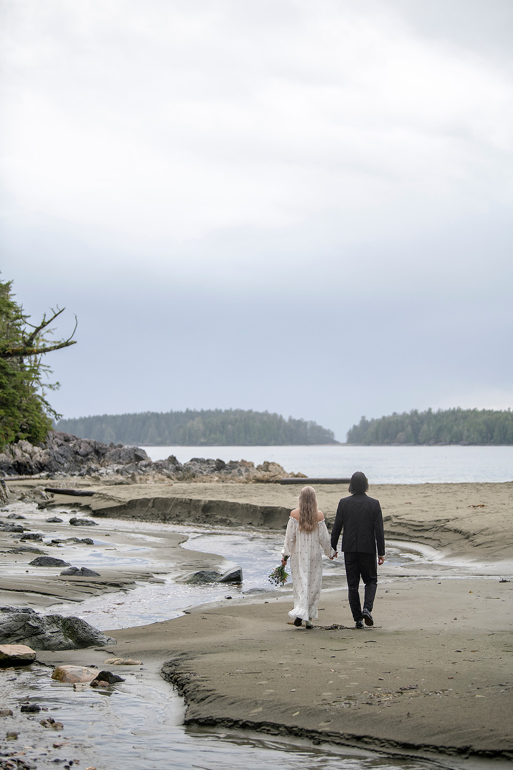 Newly married couple on the beach at their Tofino wedding on Tonquin Beach. Photographed by Tofino wedding photographer Kaitlyn Shea.