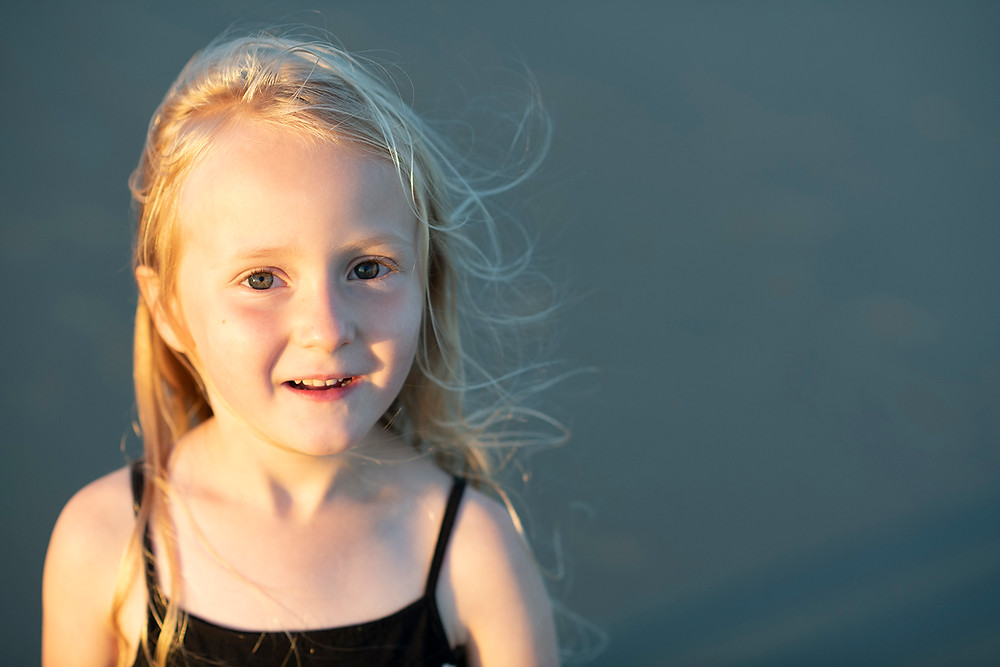 Young girl smiles during family photos in Tofino. Photographed Kaitlyn Shea.